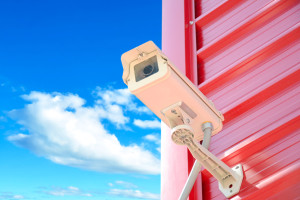 CCTV or surveillance camera on red wall